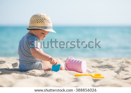 Cute baby boy playing with beach toys - stock photo