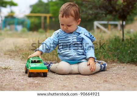 cute baby boy playing with the toy car, sitting on the ground. countryside outdoors - stock photo