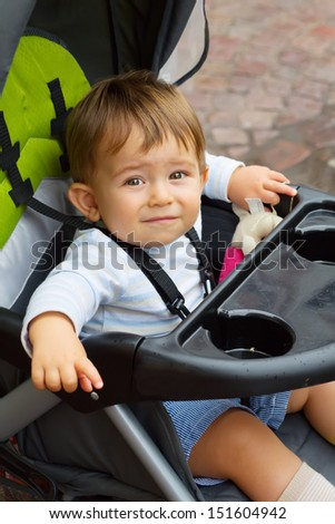 Cute Baby boy sitting in stroller outdoors