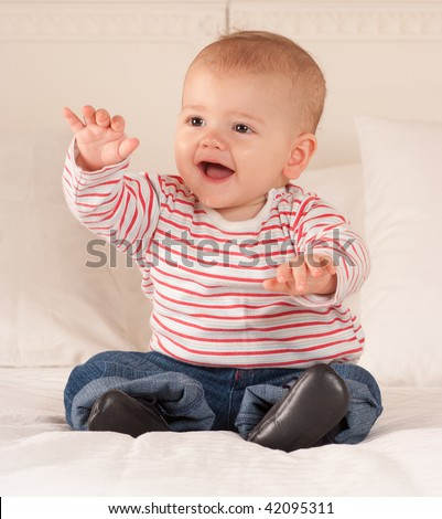 Cute baby boy sitting on a bed happily babbling - stock photo