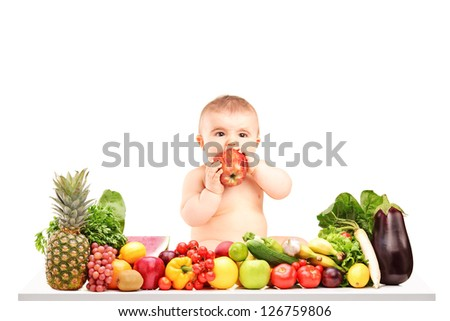Cute baby boy sitting on a table with fruits and vegetables and eating an apple isolated on white background - stock photo