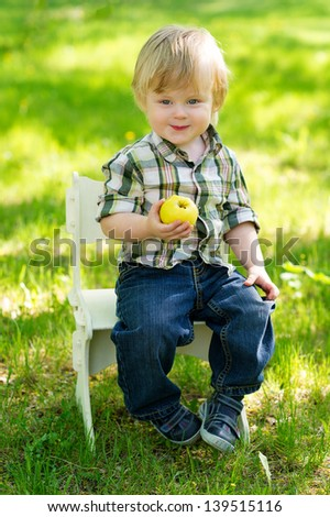 Cute baby boy sitting on the chair in the green garden and eating an apple