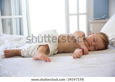 cute baby boy sleeping on bed - stock photo