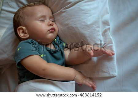 cute baby boy sleeping on the bed at home