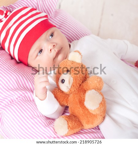 Cute baby boy sleeping with teddy bear in bed closeup - stock photo