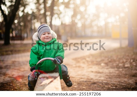 cute baby boy swinging in autumn park - stock photo