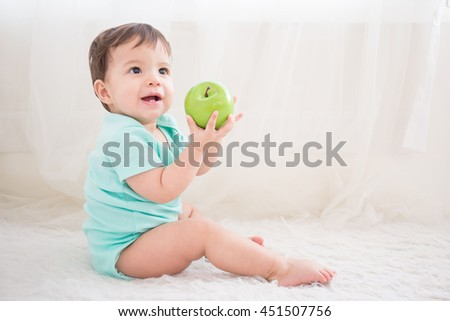 cute baby boy take  green apple sit on the white bed in bedoom, caucasian - stock photo