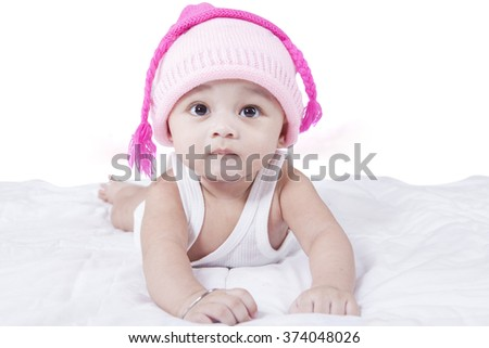 Cute baby boy wearing hat with pink color and lying on bed - stock photo
