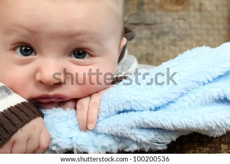 Cute baby boy with a soft blue blanket - stock photo