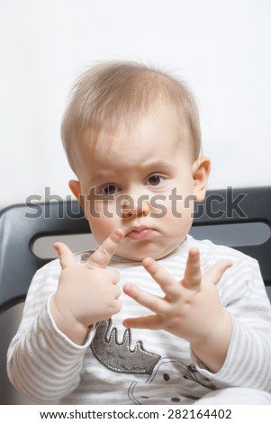 Cute baby boy with funny upset face shows seven fingers