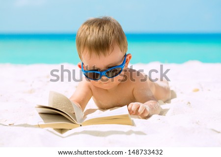 Cute baby boy with sunglasses lying on white sandy beach, reading the book and having his first tropical vacation.  - stock photo