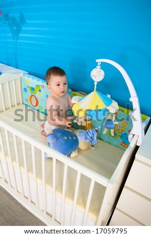 Cute baby boy ( 1 year old ) playing in baby bed at children's room, looking up. - stock photo