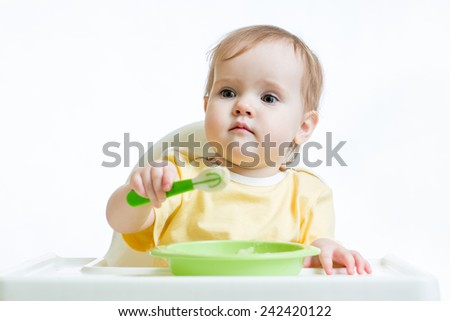 cute baby child sitting in chair with a spoon