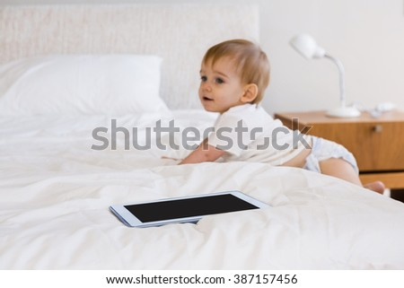 Cute baby climbing down the bed in bedroom - stock photo