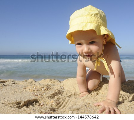 cute baby crawling on the beach - stock photo