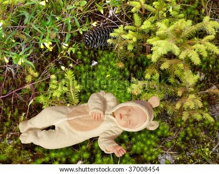 cute baby dressed in fancy dress like little mouse, sleeping on soft green moss - stock photo
