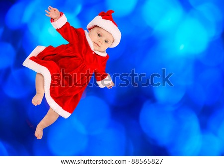 Cute baby dressed in Santa's costume flying against blue fireworks.