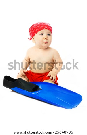 cute baby dressed in summer clothes sitting on the floor with blue flippers - stock photo