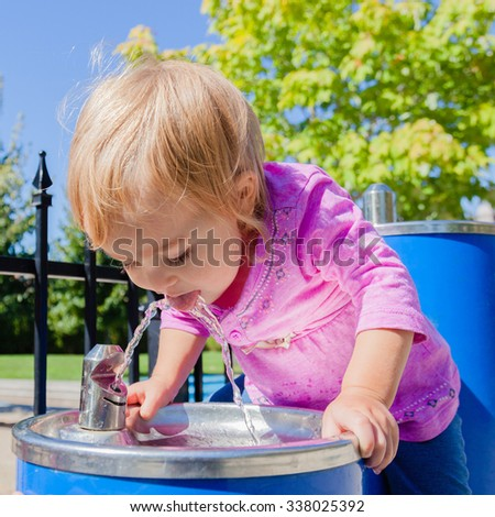 Cute baby drinking from water drinking fountain in summer. Toddler girl first attempts to do adult things. Bright sun, hard shadows. Selective focus on water stream and girls face. - stock photo