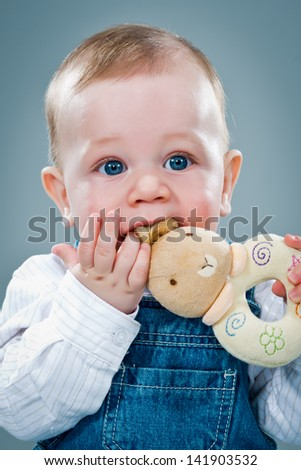 Cute Baby Eating a Toy over a Grey Background