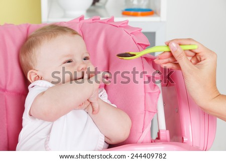 Cute baby eating fruit puree - stock photo