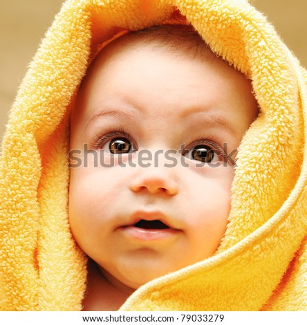 Cute baby face wrapped in towel, hygiene and health care concept - stock photo