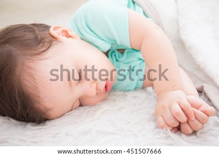 cute baby fist and sleep on the white bed in bedroom, caucasian