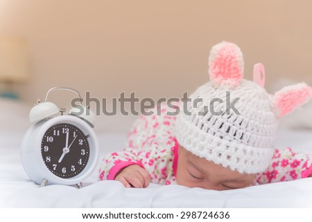 cute baby girl and alarm clock wake up in the morning. - stock photo