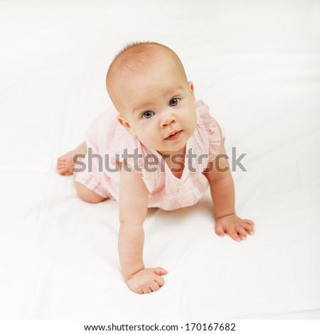 Cute baby girl crawling on the white bedding - stock photo