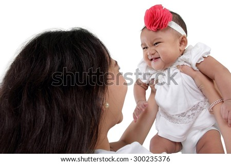 Cute baby girl giggling, hold by her mother, isolated on white background - stock photo