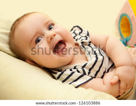 cute baby girl having fun laughing and playing toy - stock photo