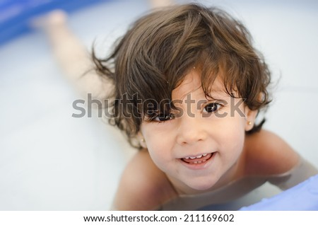 Cute baby girl in a plastic swiming pool in a low depth of field image - stock photo