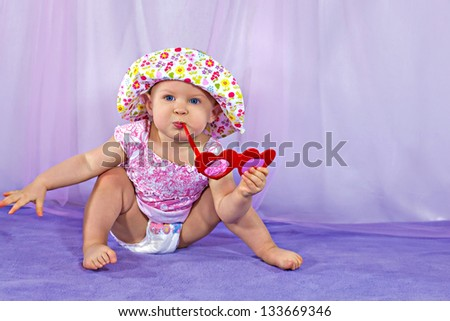 Cute baby girl in a summer hat and sunglasses