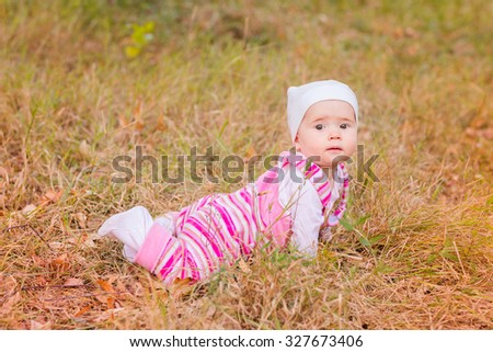 Cute baby girl in autumn leaves. First autumn - stock photo