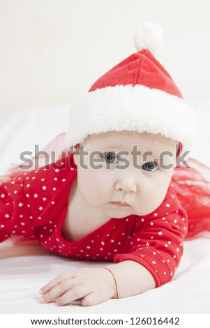 Cute Baby girl  in christmas hat laying on fur mat