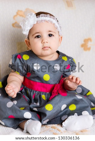 Cute baby girl in dotted dress sitting on sofa - stock photo