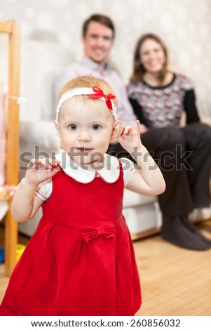 Cute baby girl in red dress and parents sitting on background - stock photo