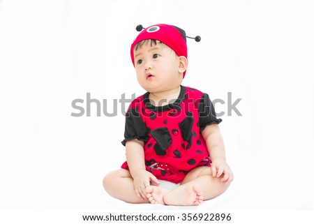 Cute baby girl in red dress isolated on a white background.