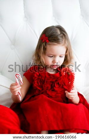 Cute baby girl in red fashionable dress sitting on white bed