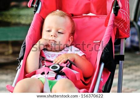cute baby girl in red stroller