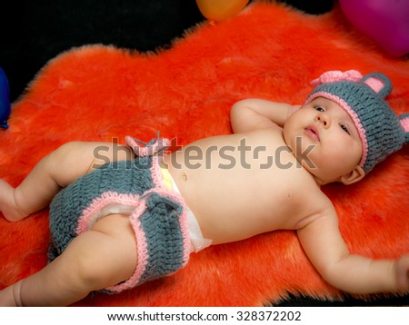 cute baby girl in the basket over black backgground