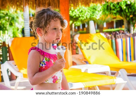 Cute baby girl is eating ice-cream - stock photo