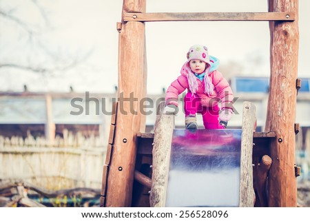 Cute Baby Girl is Getting to Slide Down on a Playground Slide - stock photo