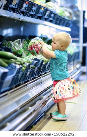 Cute baby girl is picking up radish pack from a shelf in vegetables department in a supermarket - stock photo