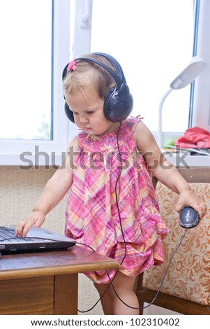 Cute baby girl listening to a music and working on the laptop