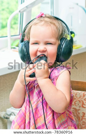 Cute baby girl listening to a music  or learning