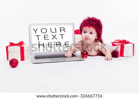Cute baby girl lying naked on her stomach on a white background next to a laptop in a red New Year's cap among red Christmas balls and red boxes with gifts picture with depth of field