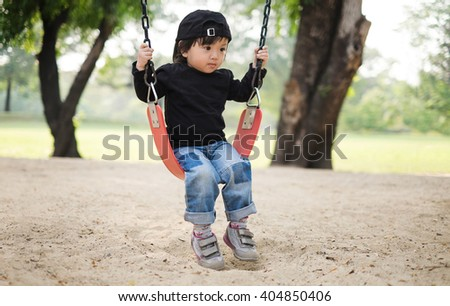 Cute baby girl playing on a swing alone - stock photo