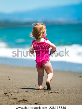 cute baby girl playing on the beach at sunset
