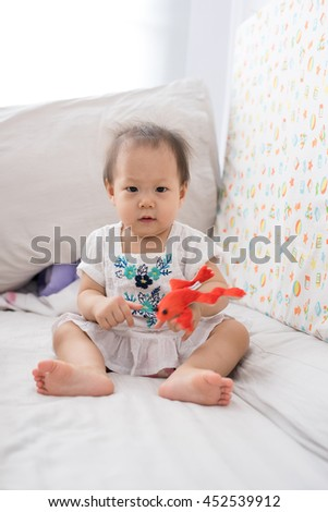 Cute baby girl playing on the bed